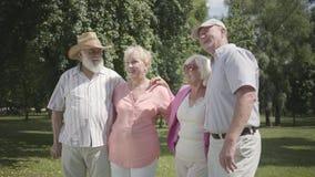 2 милых зрелых пары встречают в парке совместно Двойная дата старших пар Дружелюбная компания отдыхая outdoors r сток-видео