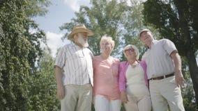 2 милых зрелых пары выглядя отсутствующий стоять в парке совместно Двойная дата старших пар Дружелюбная компания видеоматериал