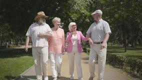2 милых зрелых пары идя в парк лета говоря и усмехаясь Двойная дата старших пар Дружелюбная компания акции видеоматериалы
