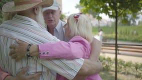 2 милых зрелых пары обнимая в парке совместно стоя в круге Двойная дата старших пар Дружелюбная компания акции видеоматериалы