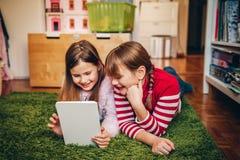 2 милых маленькой девочки играя на цифровом ПК таблетки Стоковые Фото