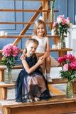 2 милых маленькой девочки с пионами 2 красивых друз имея потеху, обнимать и усмехаться Стоковое Изображение RF