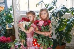 2 милых маленькой девочки с пионами 2 красивых друз имея потеху, обнимать и усмехаться Стоковые Фотографии RF