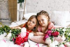 2 милых маленькой девочки с пионами 2 красивых друз имея потеху, обнимать и усмехаться Стоковое Фото