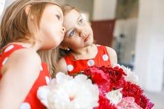 2 милых маленькой девочки с пионами 2 красивых друз имея потеху, обнимать и усмехаться Стоковое Изображение