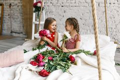 2 милых маленькой девочки с пионами 2 красивых друз имея потеху, обнимать и усмехаться Стоковая Фотография RF