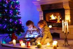 2 милых мальчика малыша, белокурые близнецы играя с новым подарком таблетки Семья празднуя праздник рождества Стоковая Фотография