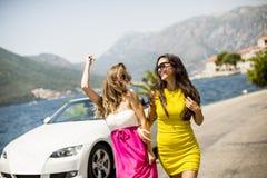 2 милых молодой женщины белым автомобилем cabriolet на взморье Стоковые Изображения