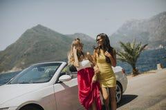 2 милых молодой женщины белым автомобилем cabriolet Стоковые Фотографии RF
