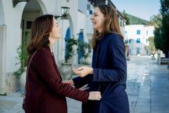 2 милых молодой женщины в пальто сини и красного вина говорят и идут I стоковая фотография rf