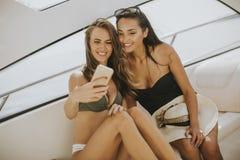 2 милых молодой женщины принимая selfie на каникулах на яхту Стоковые Изображения RF