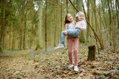 2 милых молодых сестры имея потеху во время похода леса на красивый предыдущий весенний день Активный отдых семьи с детьми стоковая фотография