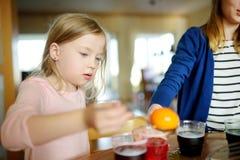 2 милых молодых сестры крася пасхальные яйца дома Дети крася красочные яйца для охоты пасхи Дети получая готовый для пасхи стоковое изображение rf