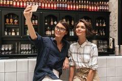 2 милых усмехаясь женщины делая selfie Стоковые Изображения