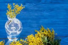 Мимоза на деревянной предпосылке в стеклянной насмешке вазы вверх Стоковые Фото
