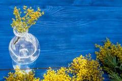 Мимоза на деревянной предпосылке в стеклянной насмешке вазы вверх Стоковые Фотографии RF