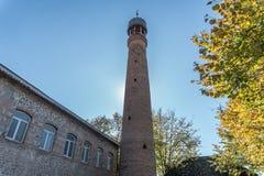 Минарет мечети Juma против твердого голубого skey стоковое изображение