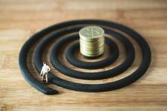 Миниатюрная диаграмма бизнесмены идя вокруг с золотыми монетками Стоковое Фото