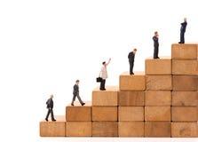 Миниатюрная диаграмма бизнесмен людей стоя на деревянном блоке стоковое фото rf