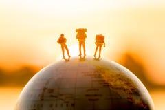Миниатюрная диаграмма люди укладывает рюкзак положение на глобусе с заходом солнца Стоковая Фотография RF