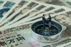 миниатюрная диаграмма handshaking и положение бизнесменов на компасе Стоковые Изображения RF