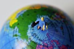 Миниатюрная женщина путешественника на верхней части мир Стоковая Фотография