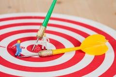 Миниатюрная игрушка работника на красной доске дротика с стрелкой дротика Стоковая Фотография RF