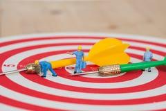 Миниатюрная игрушка работника на красной доске дротика Стоковая Фотография