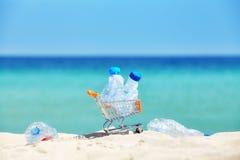 Миниатюрная магазинная тележкаа с пластичными бутылками на тропическом пляже Стоковые Изображения