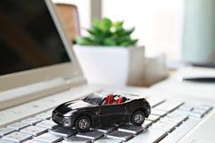 Миниатюрная модель автомобиля на компьтер-книжке компьютера Стоковая Фотография