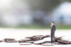 Миниатюрная модель бизнесмена на куче монеток стоковое изображение