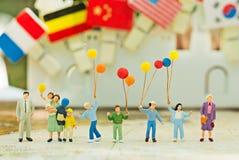Миниатюрная семья используя как день предпосылки международный концепции семей Стоковое Изображение