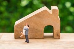 Миниатюрная счастливая семья пар стоя с деревянным домом как упорка стоковая фотография rf