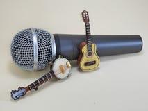 Миниатюрное банджо и миниатюрная акустическая гитара подпиранные вверх на динамическом микрофоне стоковые фотографии rf