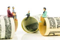 Миниатюрное обсуждение figurines на краю 100 банкнот доллара Стоковая Фотография RF