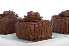 Миниатюрное пирожное шоколада испечет на белой плите, розах шоколада Стоковое Изображение RF
