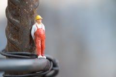 Миниатюрное положение занятия работника людей на стальном поляке стоковые фото