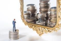 Миниатюрные бизнесмены видят финансового советника в зеркале стоковые изображения