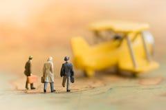 Миниатюрные бизнесмены: дела объединяются в команду ждать самолет на карте мира Стоковая Фотография