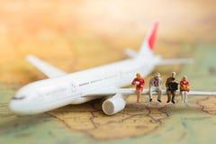 Миниатюрные бизнесмены: дела объединяются в команду ждать самолет с космосом экземпляра для перемещения по всему миру, перемещени стоковая фотография rf