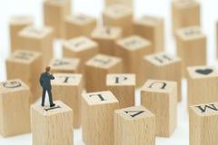 Миниатюрные бизнесмены людей анализируют положение на деревянных словах с Стоковые Изображения