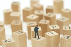 Миниатюрные бизнесмены людей анализируют положение на деревянных словах с Стоковые Фото