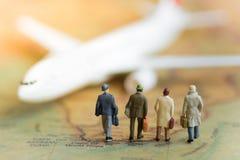 Миниатюрные бизнесмены: самолет команды дел ждать на карте мира используя как перемещение предпосылки Стоковое фото RF