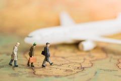 Миниатюрные бизнесмены: самолет команды дел ждать на карте мира используя как перемещение предпосылки Стоковая Фотография RF