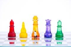 Миниатюрные бизнесмены с красочным стеклянным шахмат, стоковая фотография rf