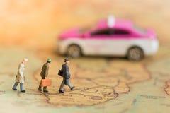 Миниатюрные бизнесмены: такси команды дел ждать на карте мира используя как перемещение предпосылки, командировку Стоковое Изображение RF