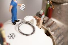 миниатюрные водопроводчики ремонтируя термостат Стоковое Изображение