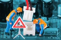 Миниатюрные инженеры исправляя соединитель провода Стоковая Фотография