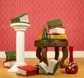 Миниатюрные книги и вазы на таблице Стоковая Фотография