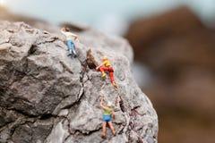 Миниатюрные люди: Альпинист смотря вверх пока взбирающся бросать вызов стоковое фото